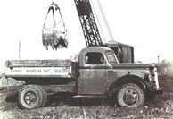 Vintage photo of a truck with crane filling the bed